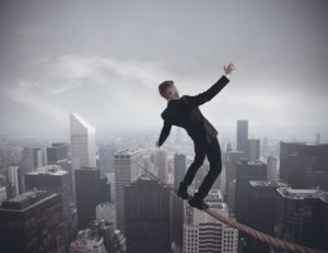 manager walking a tightrope over large city